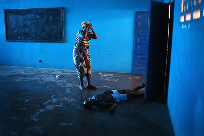 Umu Fambulle stands over her husband Ibrahim after he weakly got to his feet and fell, knocking him unconscious in an Ebola holding center on August 15, 2014 in the West Point township of Monrovia, Liberia. He died the same day. The Liberian capital was quickly overwhelmed by the epidemic in late summer, as the Ebola virus moved from a rural to an urban environment, making Monrovia the Ebola epicenter in West Africa. Only a decade after a long civil war, Liberia's fragile health system was unable to cope, international agencies were slow to react, and fear gripped the nation.
